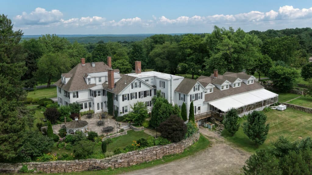 Aerial view of the inn. Large expanses of trees and manicured grounds as well as a stone patio and covered eating area.