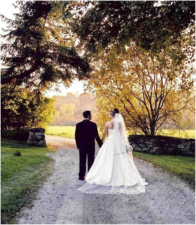 A bride wearing a white gown with her new husband in a black tux. Standing in the gravel driveway looking through a stone wall during early sunset