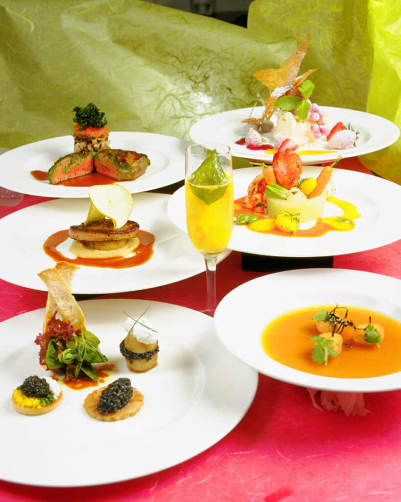 6 white plates with different types of food and a champagne glass in the middle with a mimosa.