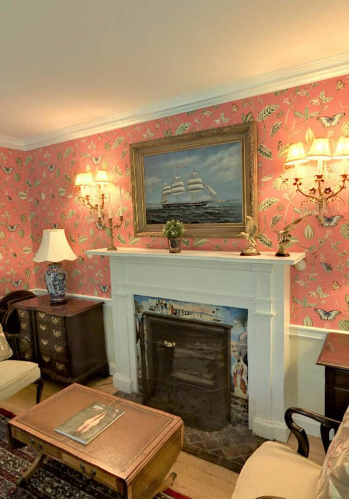 A white mantle around a fireplace with painted tiles. Pink wallpaper with various fauna and butterflies. A large ship painting above the mantle.