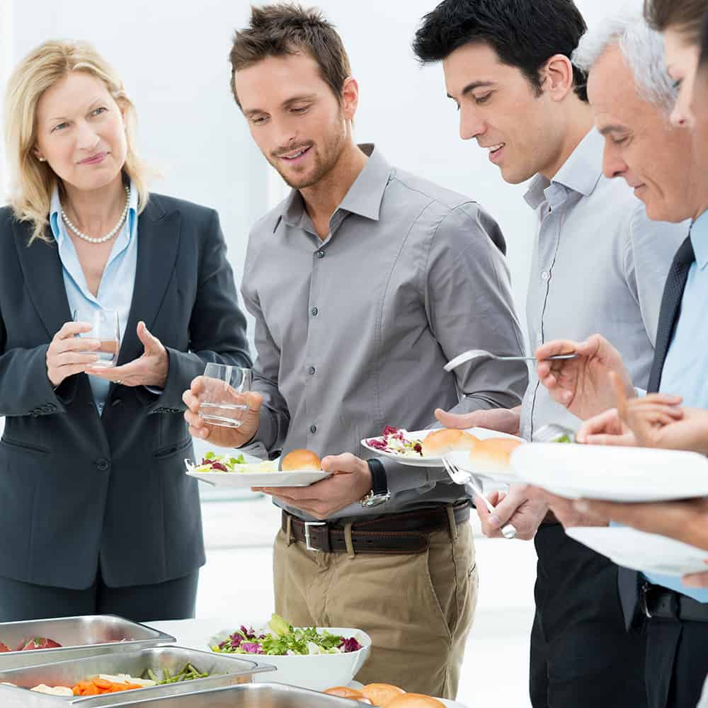 A small group of business people standing around a buffet during a business meeting