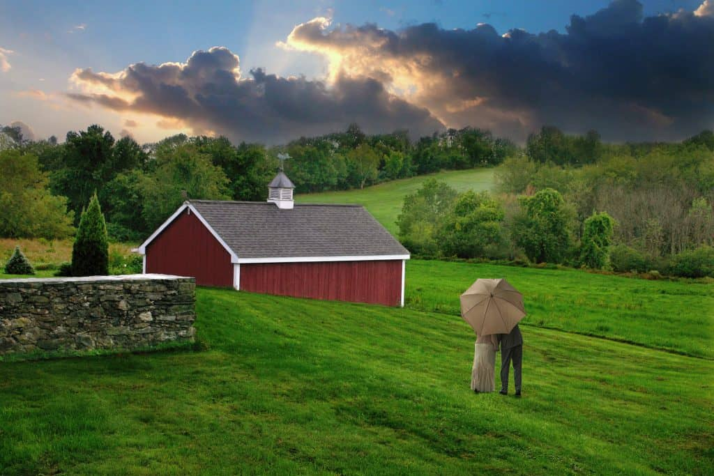 A couple standing under an umbrella in the mowed field behind the inn. Next to a stone wall and red barn with rain clouds in the distance