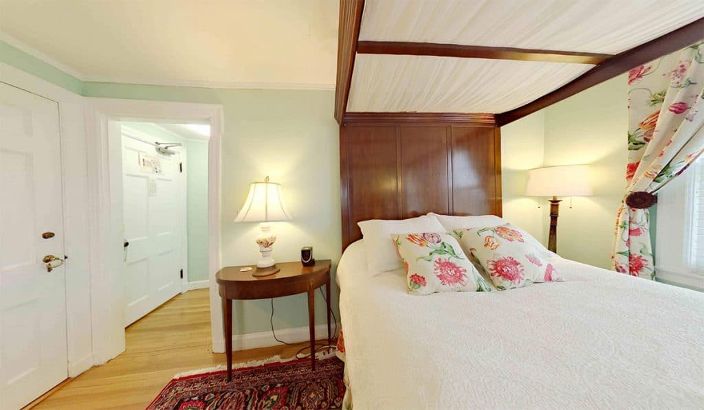 A bedroom with a canopy covered bed, floral pillows and curtains, a curved bow front side table.