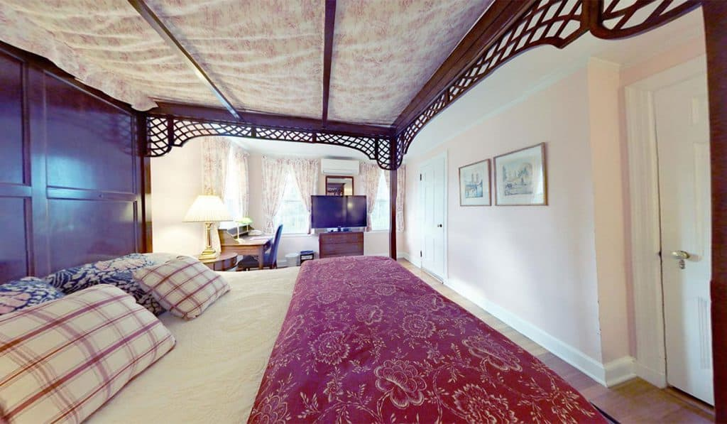 A canopy covered bed with wood lattice along the edge of the top of the bed, light pink walls with art, a desk and lots of light from the 3 windows