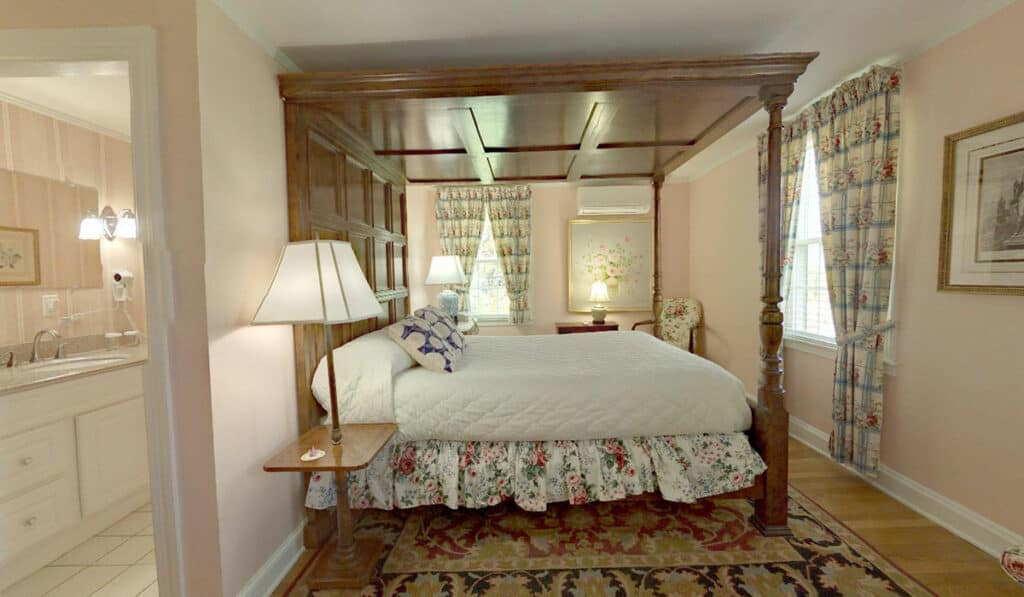 Room 201 - Queen four-poster bed, all in hardwood, with white comforter. Oriental rug and pale pink walls. Bathroom door is on the left.