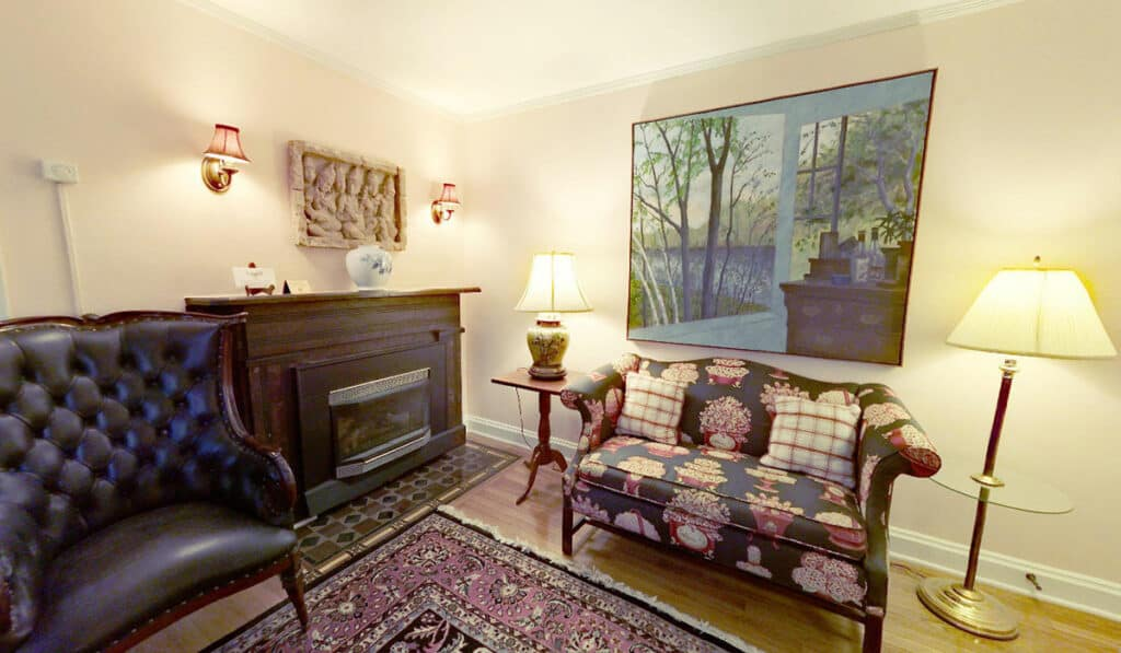 Sitting area in room 202 with loveseat, leather armchair, wood surround around gas fireplace and various artwork and lamps.