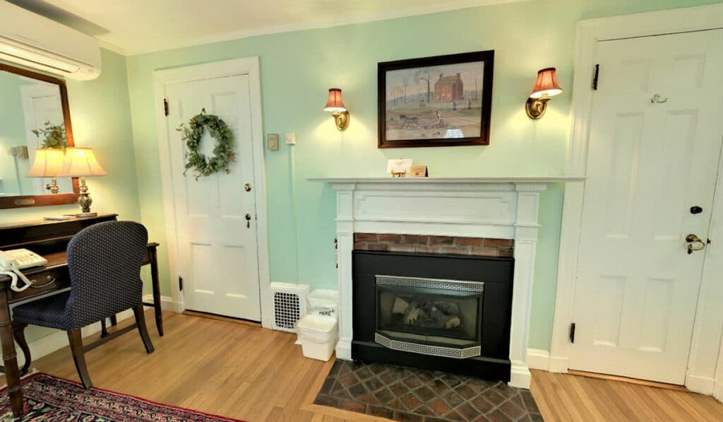 The white mantle surrounding the gas fireplace. A rustic farm scene above it between two wall lamps. The desk is to the left and the doors to the bathroom and hallway.