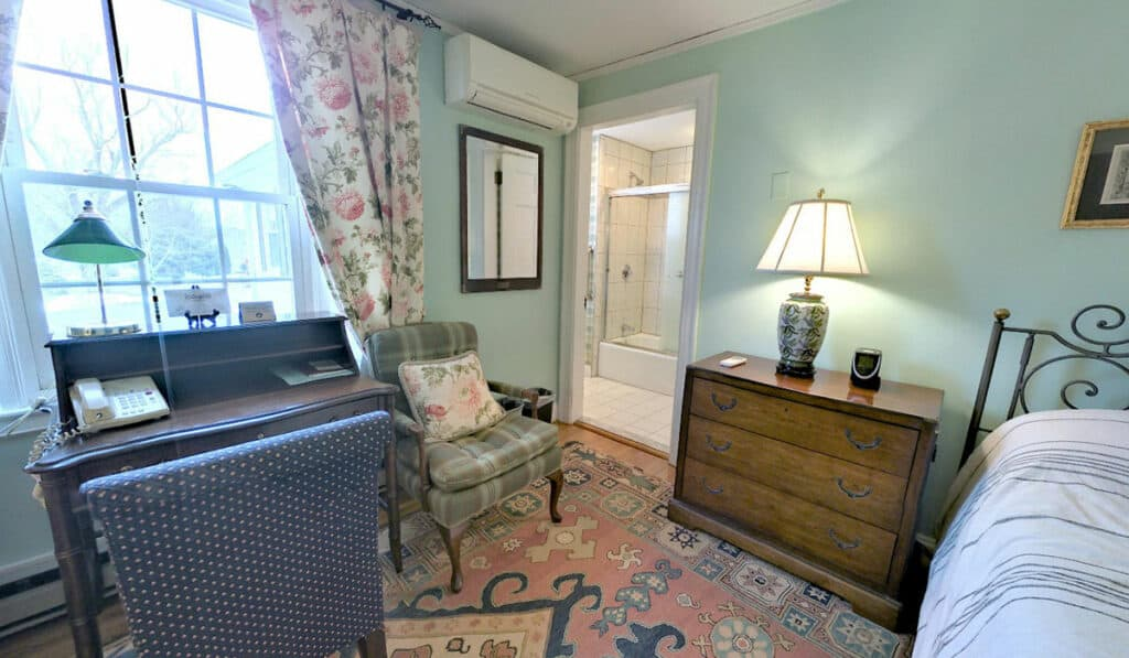 A large window with the desk below that on the left. The door to the bathroom on the right. An armchair and 3 drawer chest with lamp next to the bed.