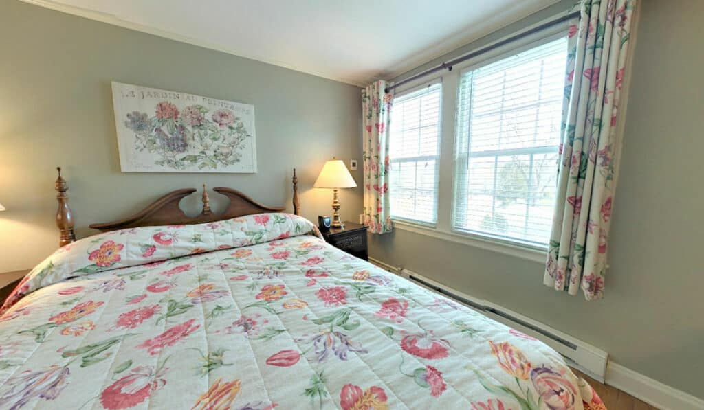 Old fashioned floral comforter with a floral print next to 2 large light filled windows