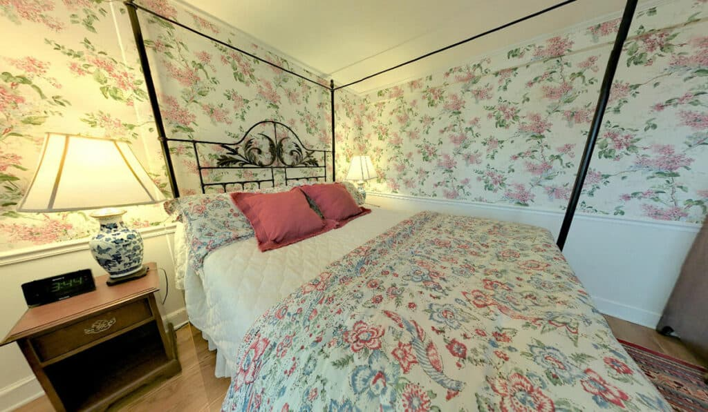 Pink floral wall paper with a metal 4 poster bed. 1 drawer bedside table with oriental style table lamp