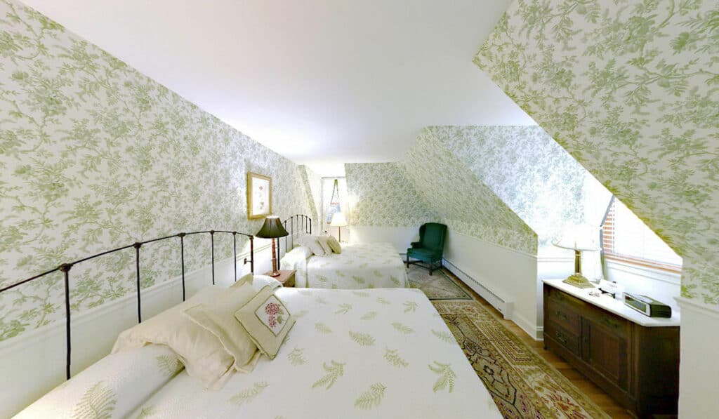 Two queen sized beds with wire headboard. Green fauna print wallpaper, credenza under a large window