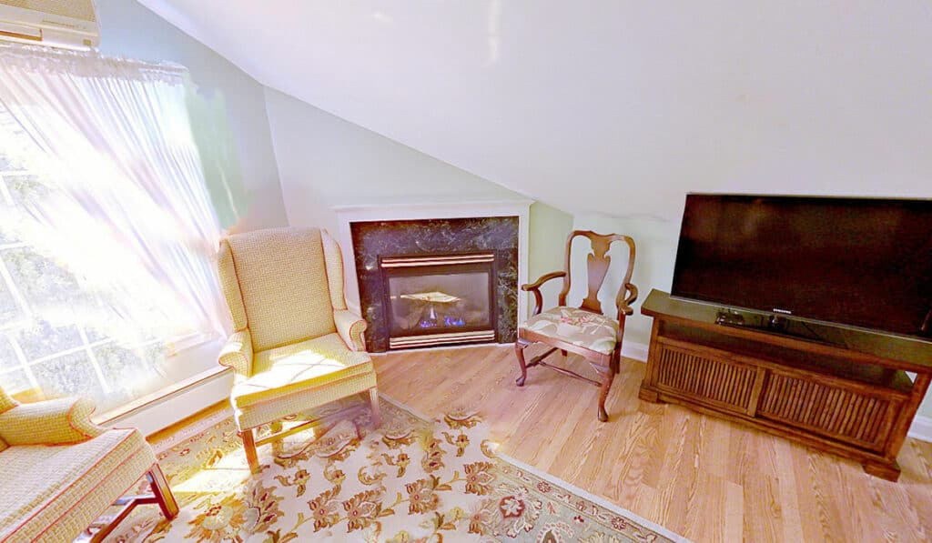 large window with sheer curtains next to a gas fireplaces, large LED television and 3 side chairs