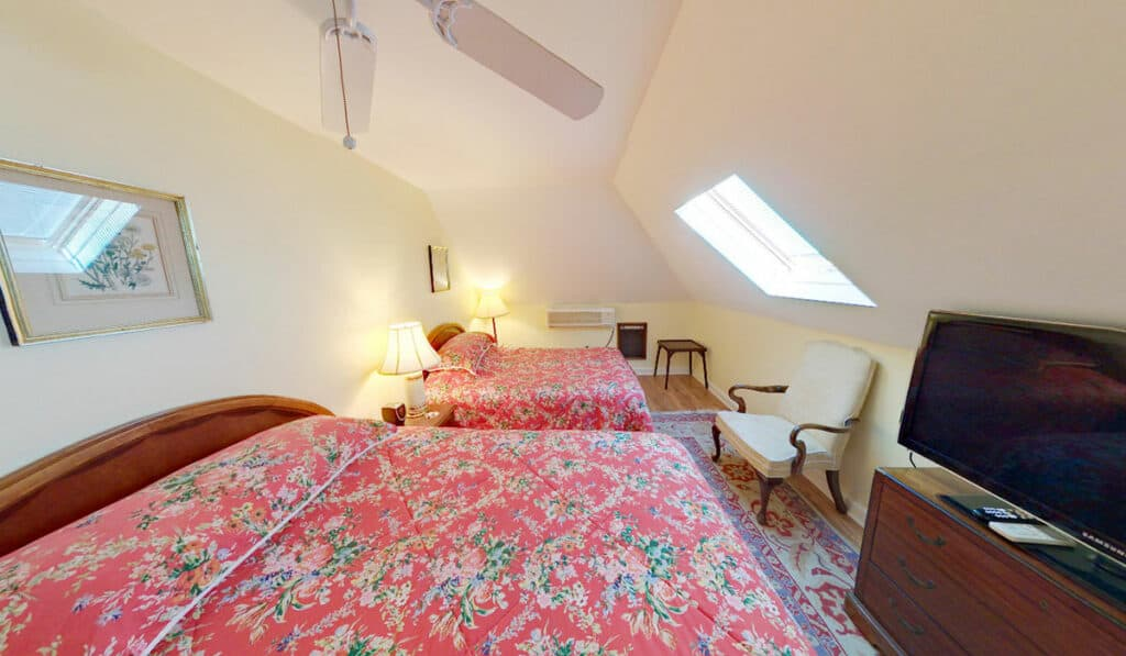 2 double beds with pink floral comforters, dresser with television, skylight, ceiling fan and chair