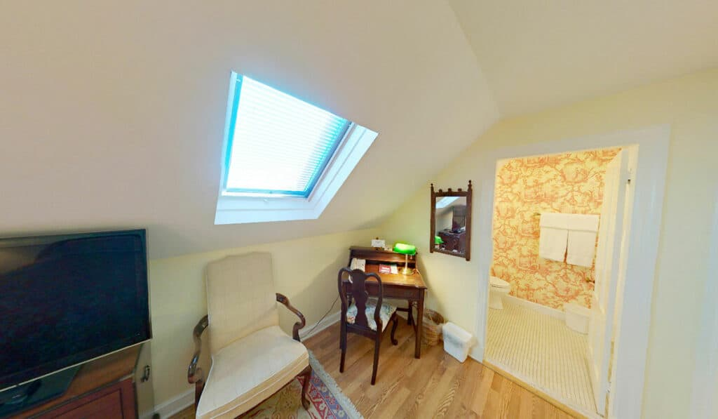 White room with slanted ceiling and skylight. With television, chair, desk and the door to the bathroom
