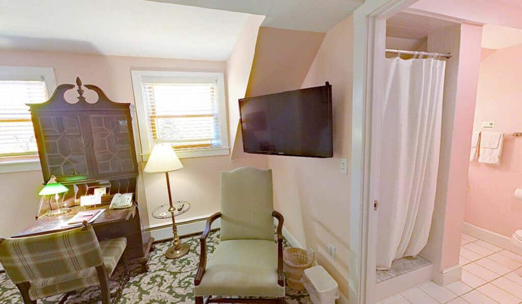 A bow front desk with hutch. 2 chairs and a tv on the wall. The bathroom door is to the right and shows the shower curtain in front of the shower.