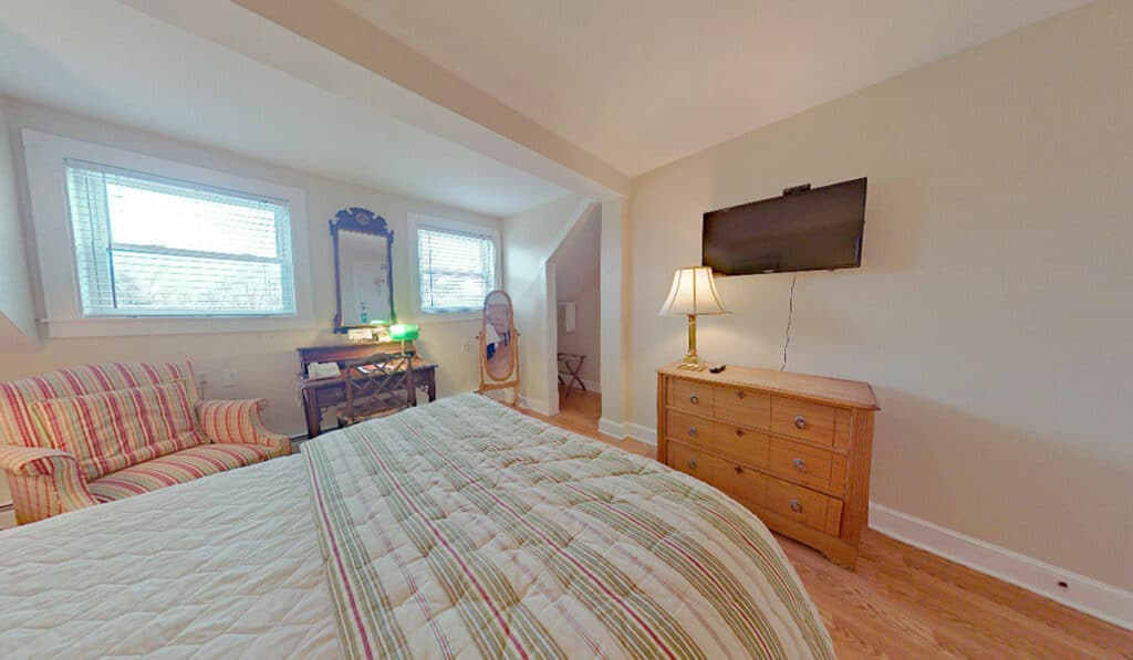 Room 213 - looking towards the foot of the bed at the tv, 3 drawer dresser with lamp, and floor mirror.